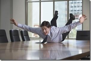 Businessman Sliding On Conference Table
